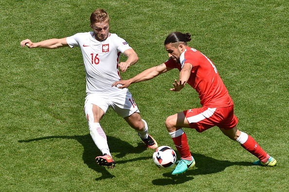 Switzerland's defender Ricardo Rodriguez (R) vies for the ball with Poland's midfielder Jakub Blaszczykowski during the Euro 2016 round of sixteen football match Switzerland vs Poland, on June 25, 2016 at the Geoffroy Guichard stadium in Saint-Etienne. / AFP / JEAN-PHILIPPE KSIAZEK        (Photo credit should read JEAN-PHILIPPE KSIAZEK/AFP/Getty Images)