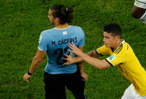 Colombia's midfielder James Rodriguez (R) runs past Uruguay's defender Martin Caceres (C) as he celebrates his second goal during the Round of 16 football match between Colombia and Uruguay at The Maracana Stadium in Rio de Janeiro on June 28, 2014, during the 2014 FIFA World Cup.   AFP PHOTO / FABRIZIO BENSCH/POOL        (Photo credit should read FABRIZIO BENSCH/AFP/Getty Images)