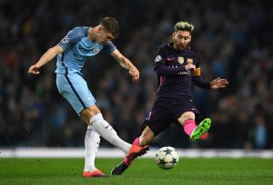 MANCHESTER, ENGLAND - NOVEMBER 01:  John Stones of Manchester City (L) shoots while Lionel Messi of Barcelona (R) attempts to block during the UEFA Champions League Group C match between Manchester City FC and FC Barcelona at Etihad Stadium on November 1, 2016 in Manchester, England.  (Photo by Shaun Botterill/Getty Images)